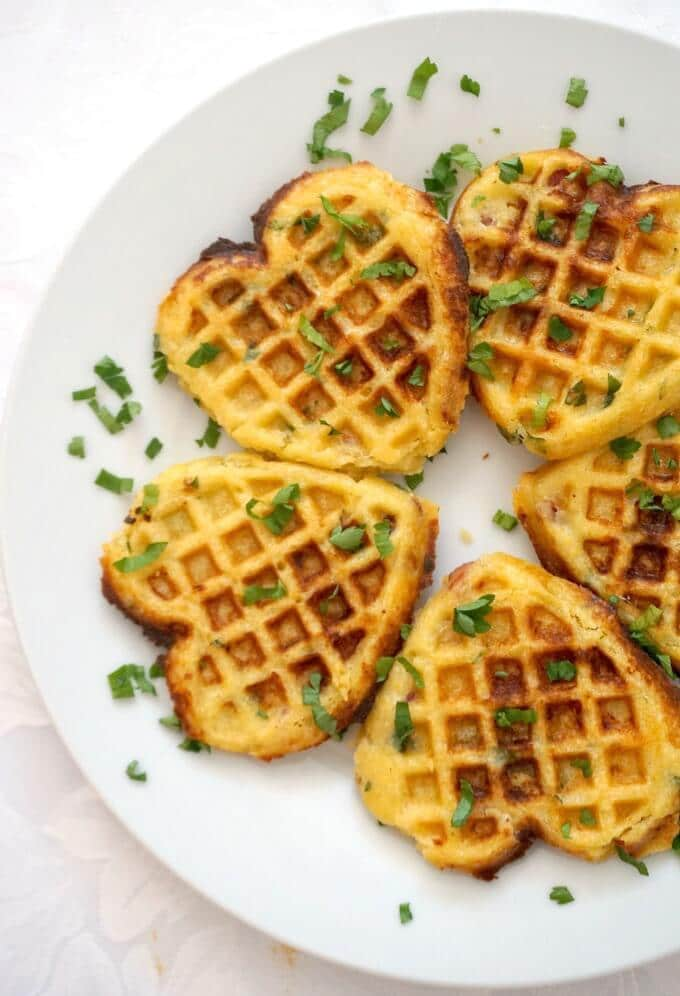 Overhead shoot of a white plate with 5 cornbread waffles garnished with chopped parsley