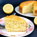 A slice of lemon drizzle cake on a small plate, with another plate with cake in the background
