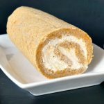A pumpkin roll with cream cheese filling on a white plate