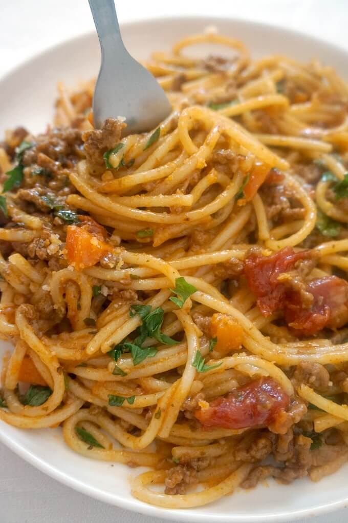 Overhead shoot of a white plate with spaghetti bolognese