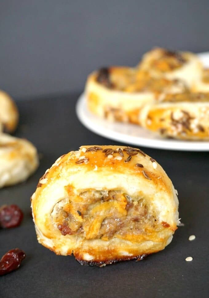 A mini puff pastry sausage roll with a plate of more rolls in the background