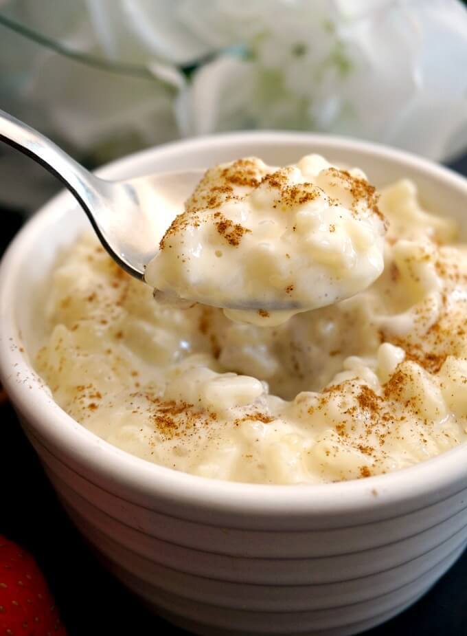 A rameskin of rice pudding with a teaspoon scooping pudding