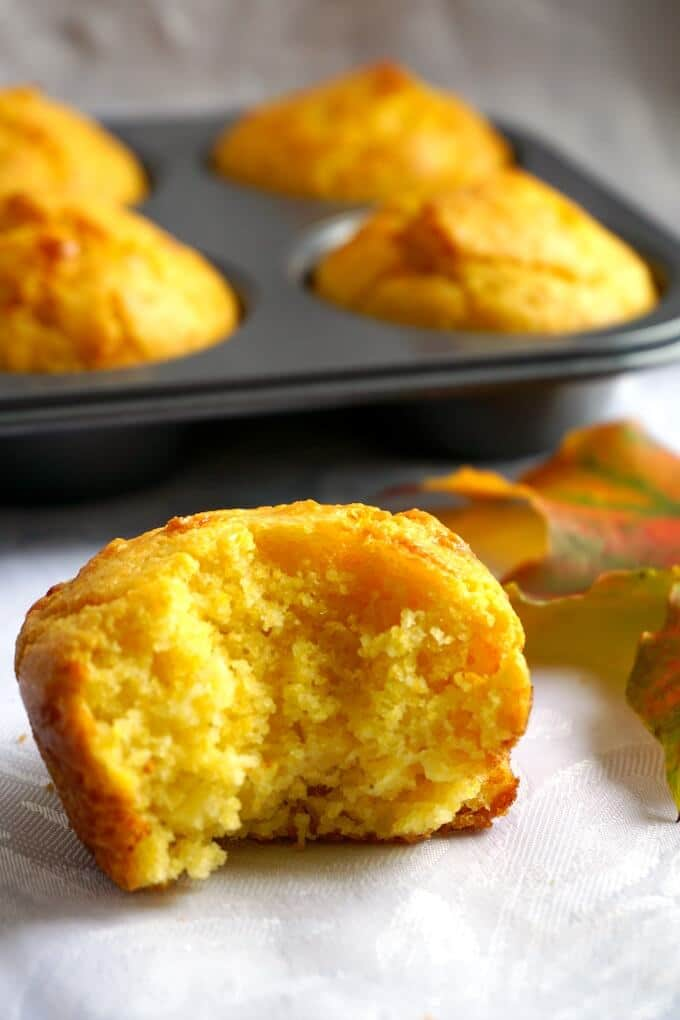 A ha;f a cornbread muffin with a muffin tin of cornbread muffins in the background