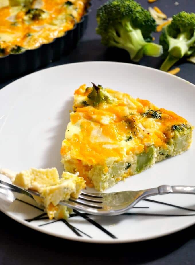 A white plate with a slice of Low Carb Crustless Broccoli and Cheese Quiche and a fork