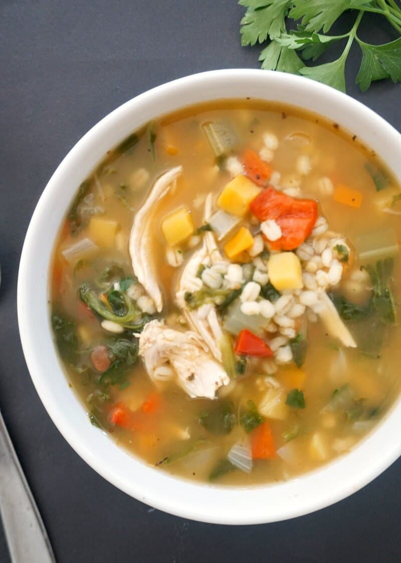 Overhead shot of a white bowl of chicken and barley soup