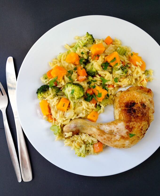 Overhead shot of a white plate with Roasted Chicken Leg Quarters with Vegetable Orzo
