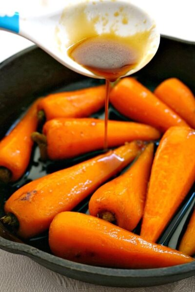 A skillet with Soy Honey Glazed Baby Carrots and glazed being drizzled over them
