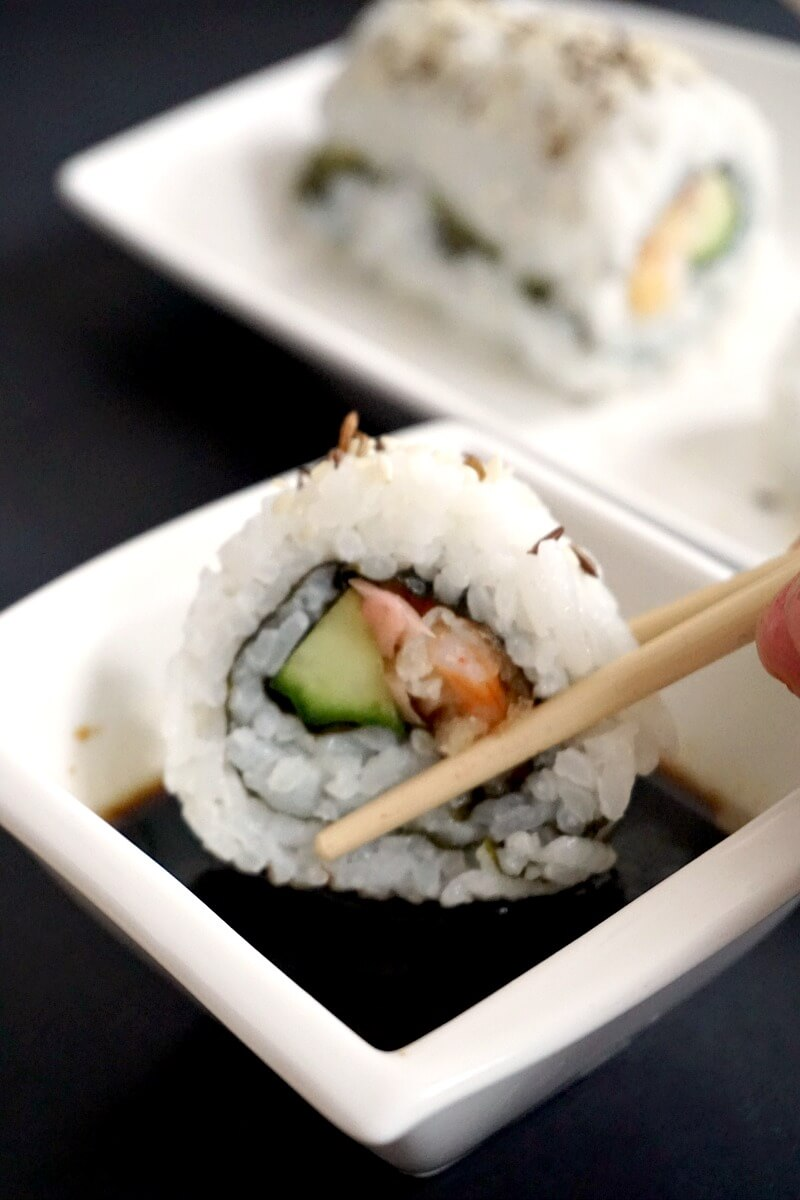 A shrimp tempura roll being dipped in soy sauce