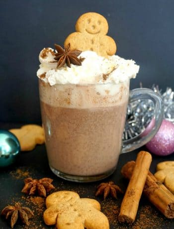 A cup of Gingerbread Hot Chocolate with spices around it