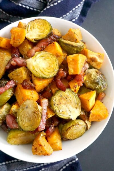 Overhead shot of a white plate with Maple Roasted Brussel Sprouts with Bacon and Sweet Potatoes