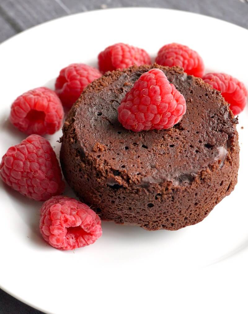 A white plate with a lava cake and raspberries around it