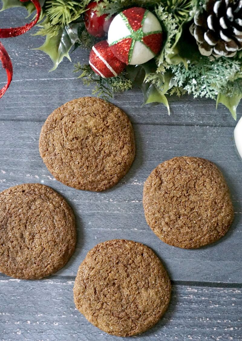 Overhead shoot of 4 ginger snap cookies and a Christmas decoration