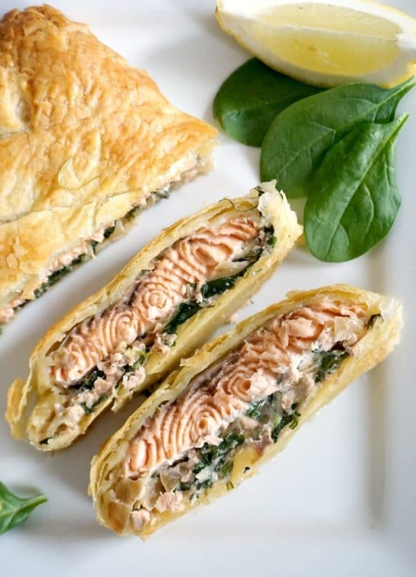 Overhead shot of a white plate with 2 slices of salmon wellington and 2 spinach leaves and