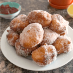 A white plate with beignets dusted with powdered sugar