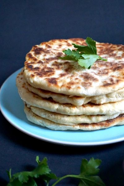 A blue -plate with a pile of 5 yogurt flatbreads