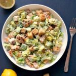 overhead shoot of a white bowl with caesar salad and croutons