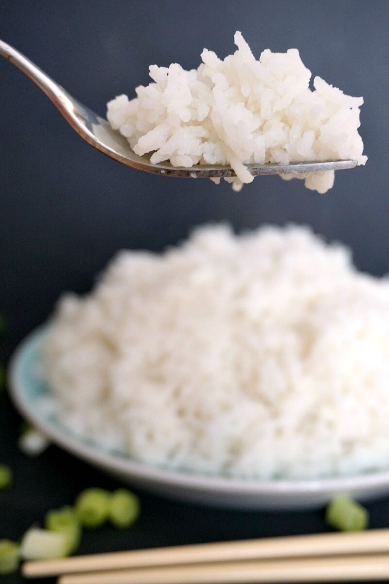 A fork with fluffy basmati rice and a plate of rice in the background