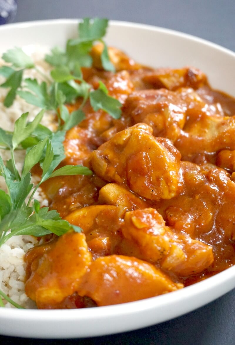 A white plate with chicken curry, rice and parsely leaves