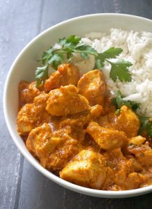 A bowl with chicken curry, rice and coriander leaves