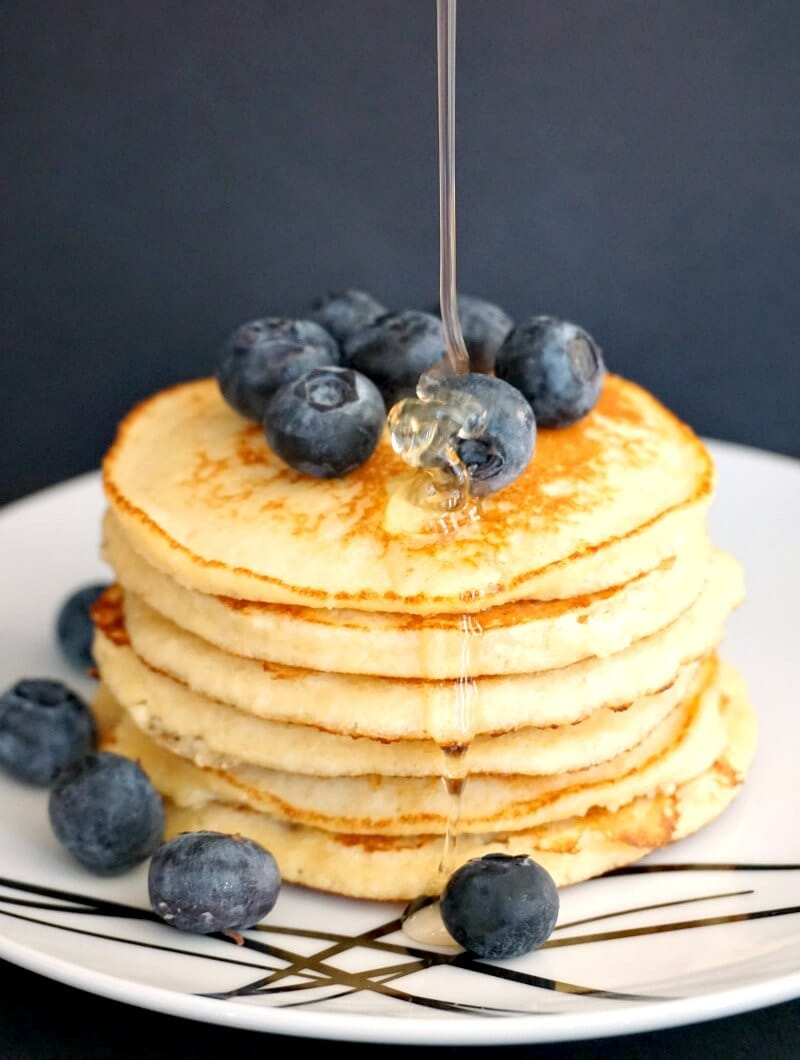 A stack of 6 almond pancakes topped with blueberries and drizzled with honey