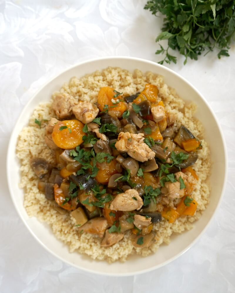 Overhead shoot of a white plate with couscous and moroccan chicken tagine