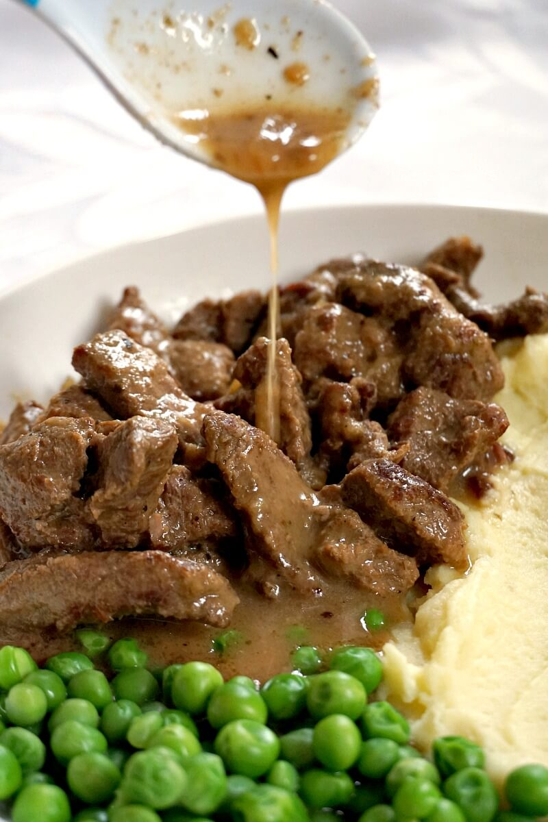 A white plate with beef tips, mashed potatoes and peas, and gravy being drizzled over the beef
