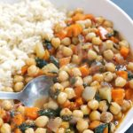 Chickpea Stew with spinach, carrots and roasted red peppers, a delicious midweek meal that is ready in only 30 minutes. Super nutritious, low in calories, and gluten free, this stew goes well with the whole family. A great meat-free dinner recipe that is vegetarian and vegan friendly too. If you are looking for recipes on a budget, this chickpea stew is the recipe for you. Comfort food for chilly days. #chickpeastew, #stew, #comfrotfood, #veganrecipes, #vegetarianrecipes, #dinnerrecipes, #easy