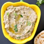 A yellow dish with baba ganoush appetizer