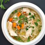 Overhead shoot of a white bowl with chicken and noodle soup made in the slow cooker