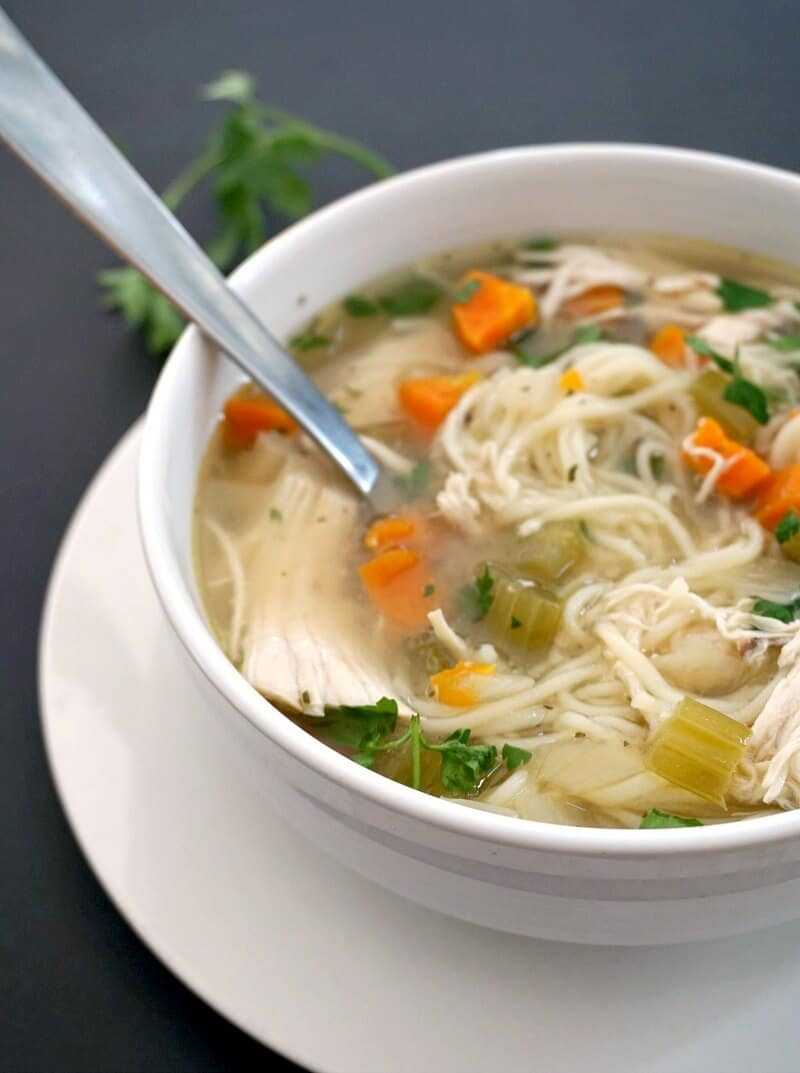 A white bowl with chicken and noodle soup made in the slow cooker