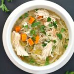 Overhead shoot of a white bowl of chicken and noodle soup made in the slow cooker