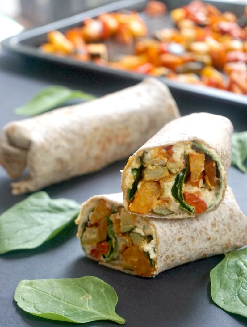 2 halves of a harissa roasted vegetable and hummus wrap, a whole wrap, spinach leaves and a tray of roasted vegetables in the background