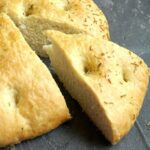 A slice cut out of a rosemary focaccia