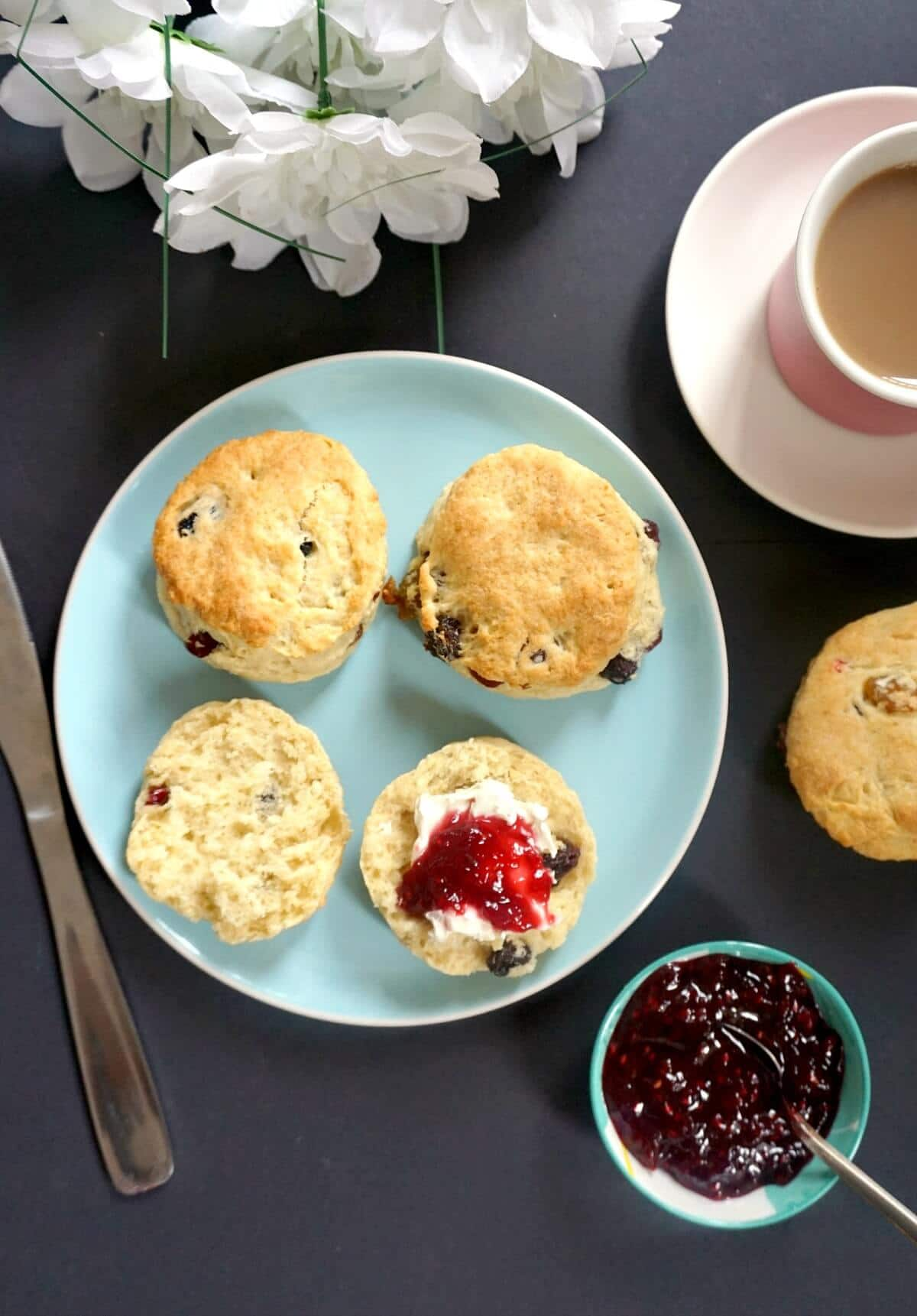 Overhead shoot of a light blue plate with 2 whole scones and 2 halves, a small bowl of jam on the side, a tea cup and a knife
