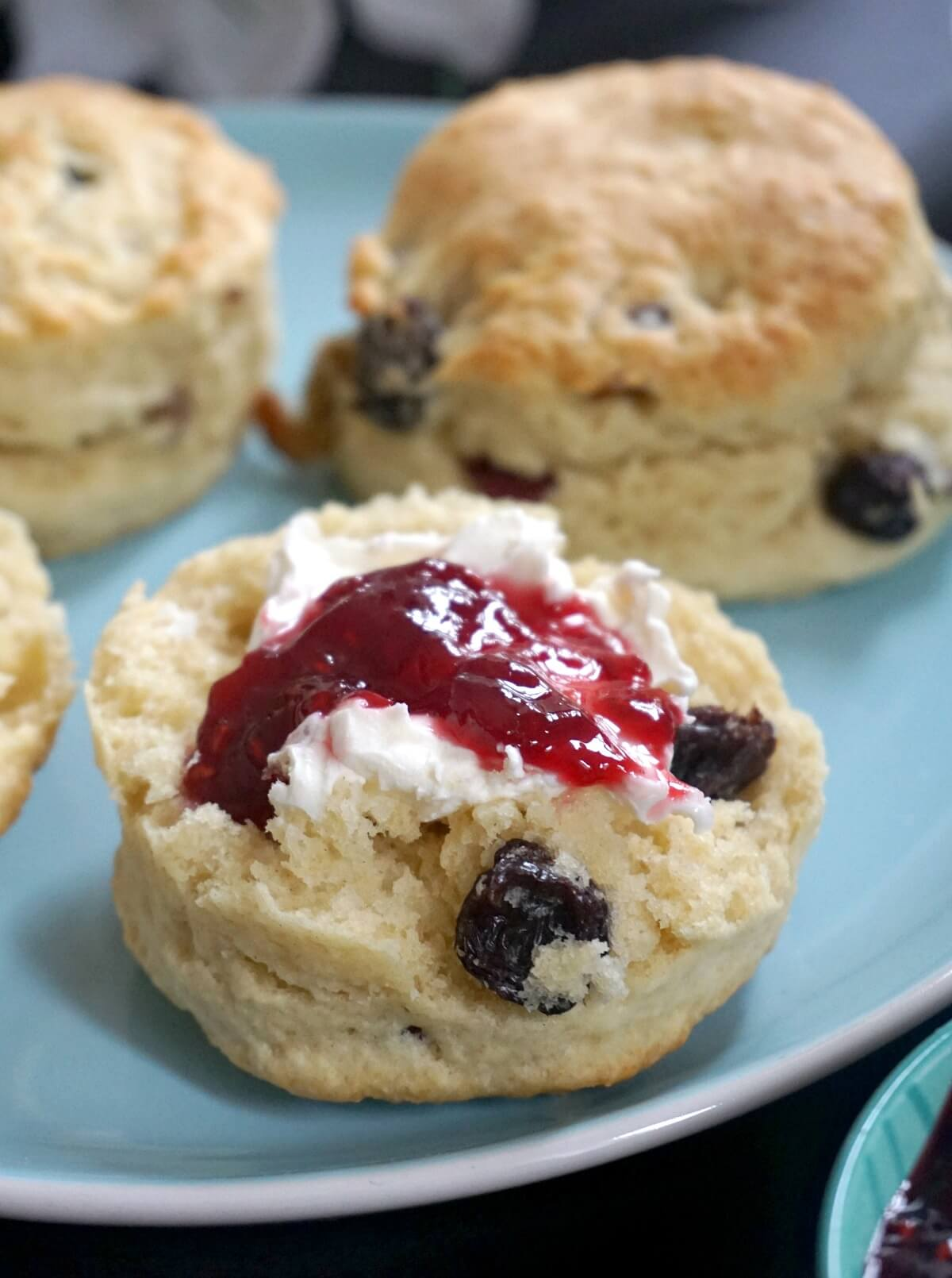 Close-up shoot of a half a scone with cream and jam