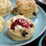 A light blue plate with 3 whole scones and half a scone with cream and jam