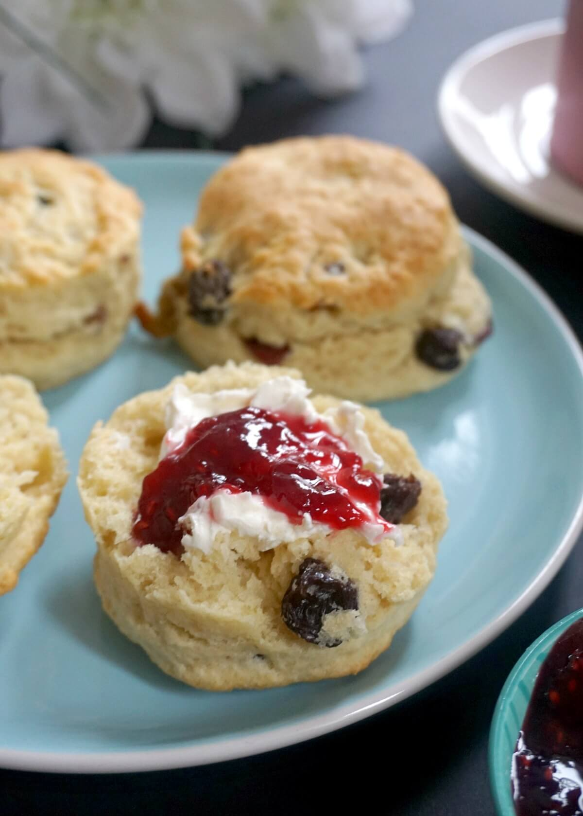 A light blue plate with 3 whole scones and half a scone topped with cream and jam