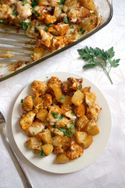 Overehead shoot of a white plate with chicken potato bake, and a casserole dish on the side