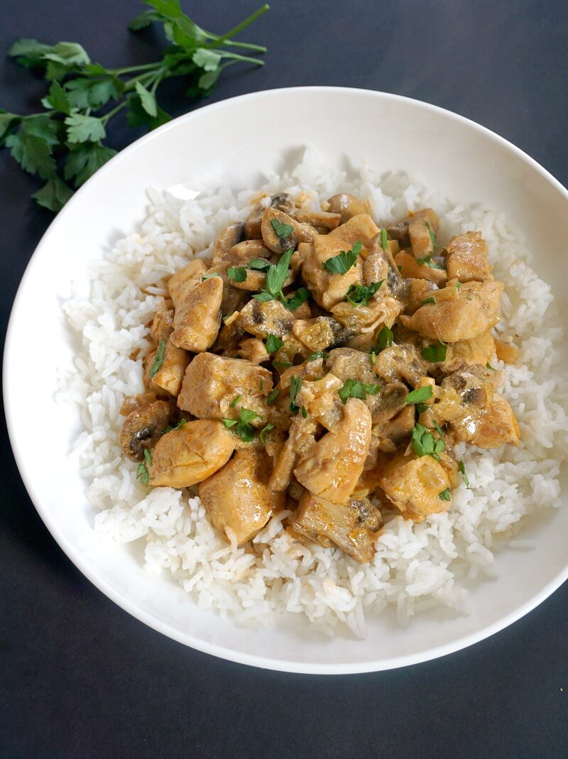 A white plate with rice and chicken stroganoff with mushrooms