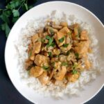 Overhead shoot of a white plate with rice and chicken and mushroom stroganoff topped with fresh parsley
