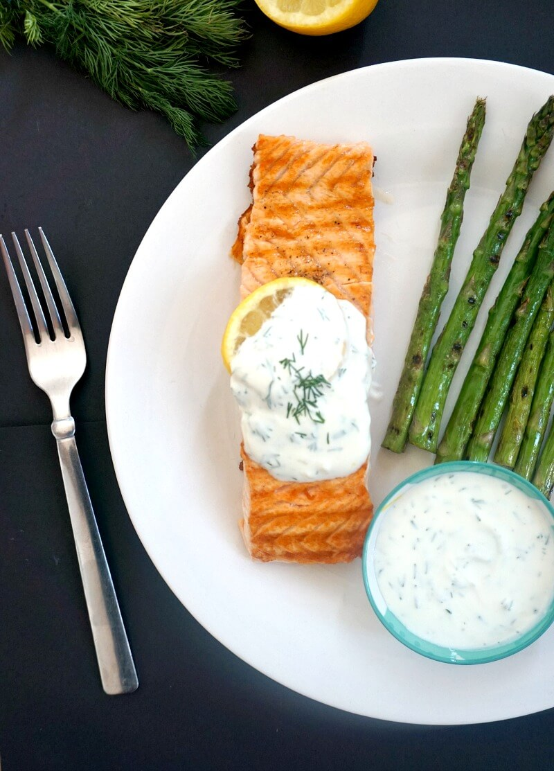 Half of a white plate with a grilled salmon fillet topped with yogurt dill sauce, grilled asparagus on the side, a fork and a bowl of sauce