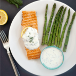 Overhead shoot of a white plate with a grilled salmon fillet topped with yogurt dill sauce, grilled asparagus on the side and a small bowl of more sauce