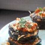 A stack of eggplant parmesan on a blue plate