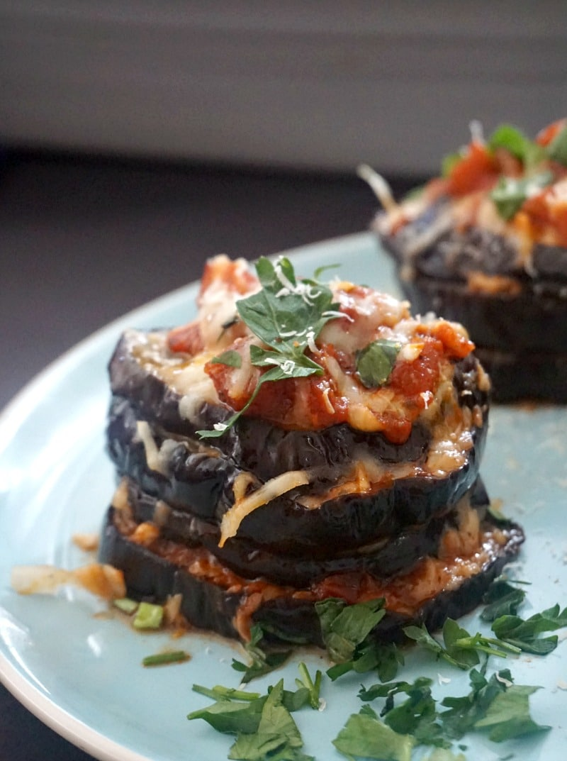A stiack of eggplant parmesan topped with cheese and fresh parsley