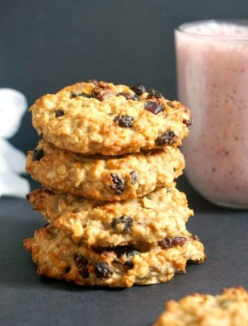 A stack of 4 cookies with a glass of smoothie in the background