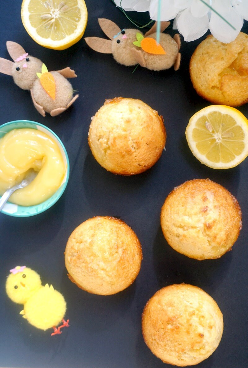 Overhead shoot of 5 lemon muffins with a small bowl of lemon curd and Easter decorations around