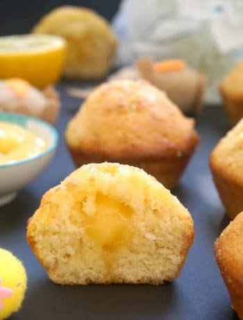 Half of a lemon drizzle muffin filled with lemon curd, with other lemon muffins around it
