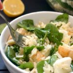 A white bowl of orzo salad with spinach, chicken and feta, and a fork into the bowl