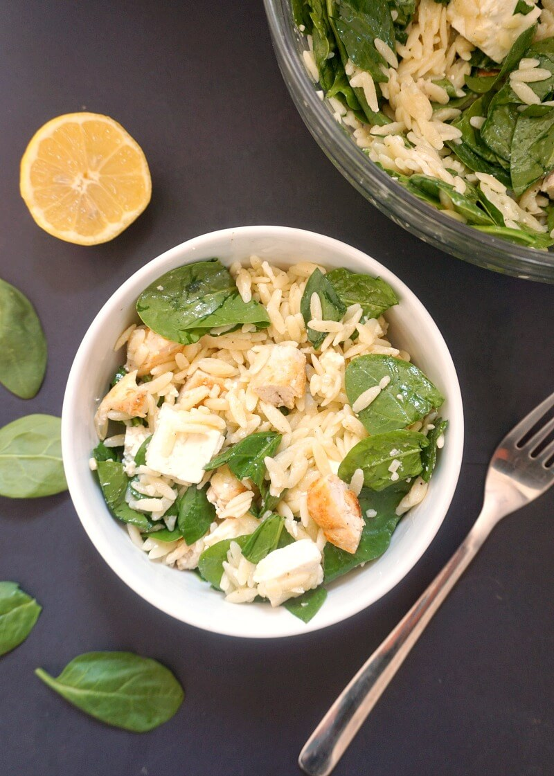 Overhead shoot of a white bowl with orzo salad, a fork on the side, half a lemon and fresh spinach leaves