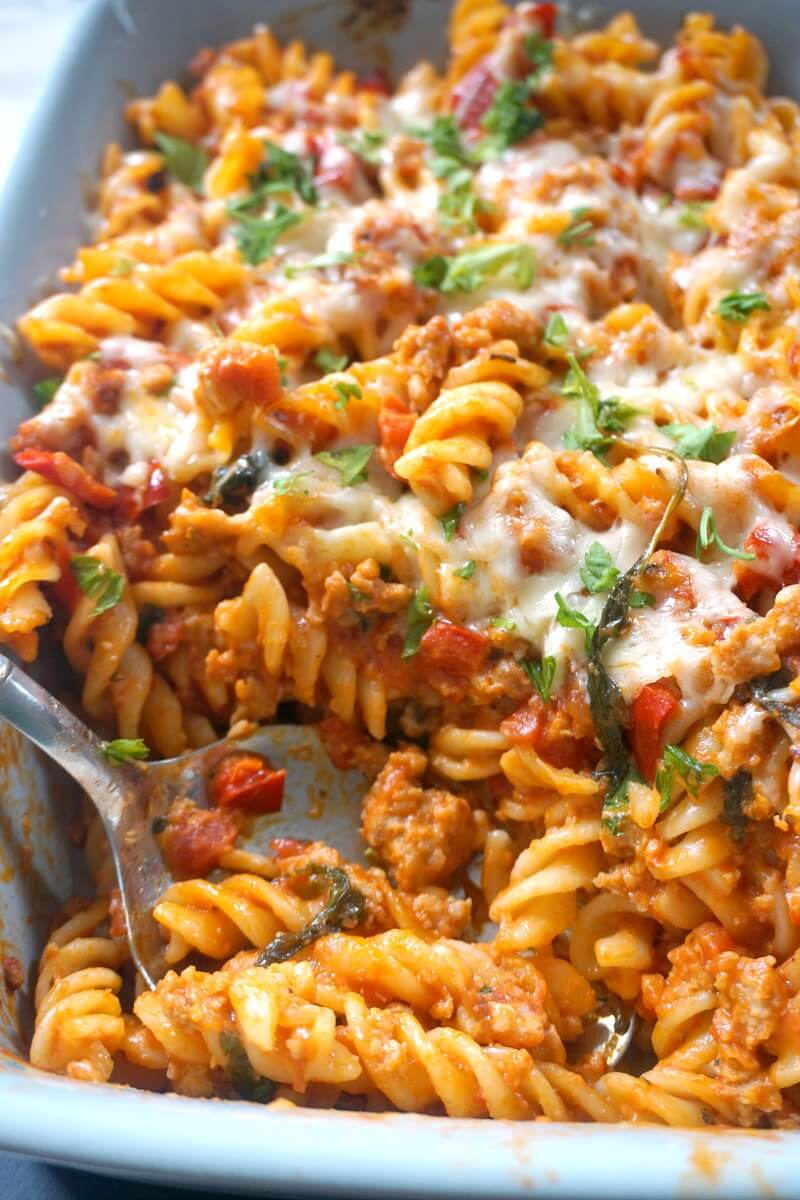 A dish with sausage pasta bake and a serving spoon in it